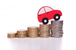 red toy car perched on stack of coins